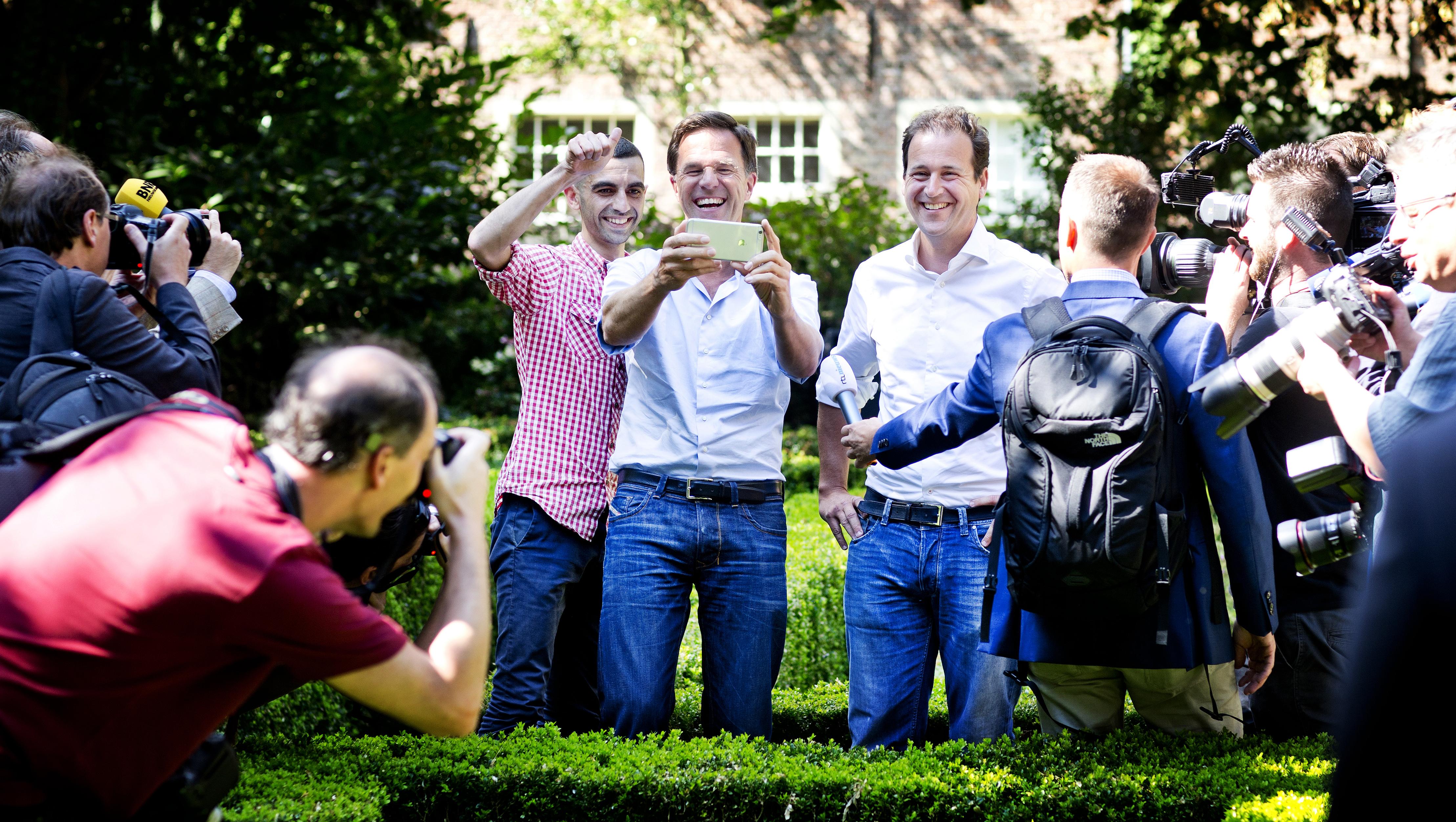 DELFT - Man (L) in de tuin van het prinsenhof maakt een praatje met Mark Rutte. Rutte vraagt: Wat ben je aan het doen. De man zegt: Oh lekker een jointje aan het roken. Vervolgens maken ze een selfie met de telefoon van de man. Casual Dagje Kabinet. Kabinet komt bijeen in het Lambert van Meerten Museum aan de Oude Delft en maakt een korte wandeling over de gracht de Oude Delft en door de binnentuin van het prinsenhof waarna de vergadering wordt voortgezet. - FOTO GUUS SCHOONEWILLE